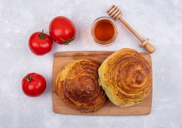 Draufsicht von aserbaidschanischem traditionellem gebäck gogal auf einem hölzernen küchenbrett mit honig auf einem glasglas mit frischen tomaten lokalisiert auf einem weißen hintergrund