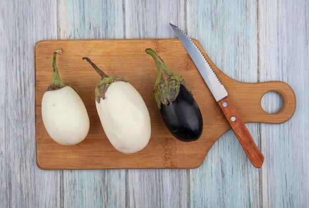 Draufsicht von auberginen und messer auf schneidebrett auf hölzernem hintergrund
