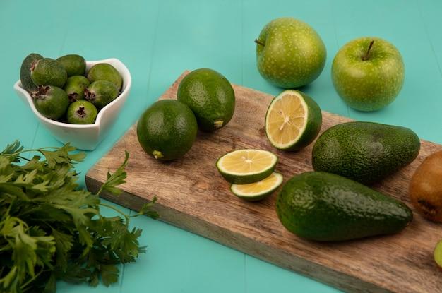 Draufsicht von birnenförmigen avocados mit limetten und kiwis auf einem hölzernen küchenbrett mit feijoas auf einer schüssel mit äpfeln und petersilie lokalisiert auf einer blauen wand