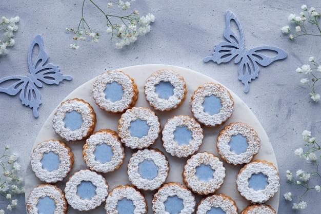 Draufsicht von blume linzer-plätzchen mit blauer glasur auf licht