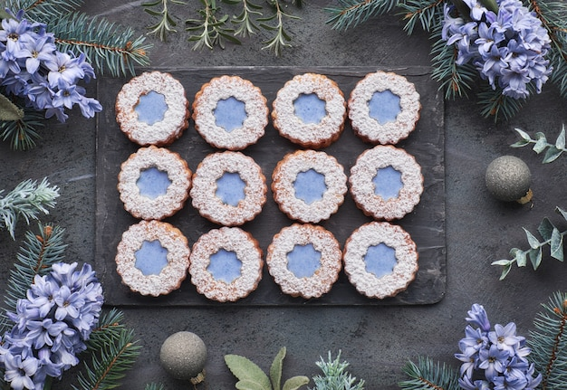 Draufsicht von blume linzer-plätzchen mit blauer verglasung auf dunklem winterhintergrund mit kräutern und blumen