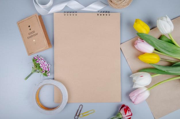 Draufsicht von braunem blatt papier mit postkarte und bunten tulpenblumen mit türkischer nelke und rose auf blauem hintergrund