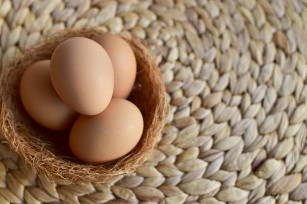 Draufsicht von braunen hühner- / hühnereiern in einem nest auf eine natürliche matte