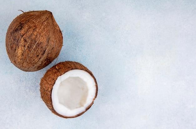 Draufsicht von braunen und frischen kokosnüssen auf weiß mit kopienraum