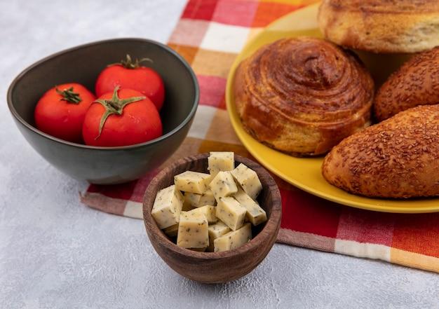 Draufsicht von brötchen auf einem gelben teller auf einem karierten tuch mit käsescheiben auf einer holzschale mit tomaten auf einer schüssel auf einem weißen hintergrund