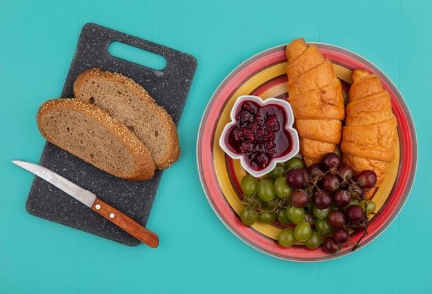 Draufsicht von broten als geernteter brauner kolben mit messer auf schneidebrett und croissants mit trauben und himbeermarmelade in platte auf blauem hintergrund
