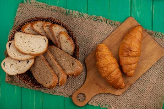 Draufsicht von broten als gesäte braune kolben- und baguettescheiben im korb und in den croissants auf schneidebrett auf sackleinen auf grünem hintergrund