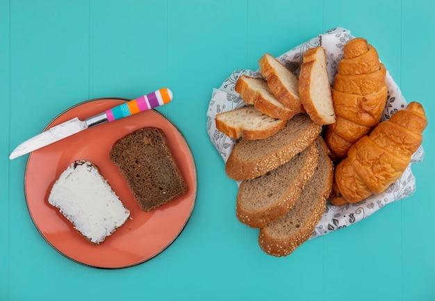 Draufsicht von broten als geschnittenes entkerntes cob-baguette und croissant in schüssel und roggenbrot verschmiert mit käse mit messer in platte auf blauem hintergrund