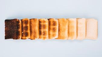 Draufsicht von Brotscheiben in verschiedenen Stadien des Röstens in Zeile auf weißem Hintergrund angeordnet