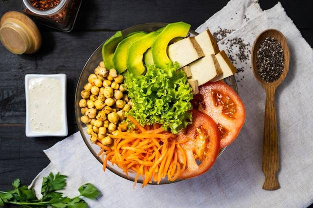 Draufsicht von buddha-schüssel auf einer rustikalen tabelle. veganes gericht aus kichererbsen, salat, gemüse, tofu und avocado, flachgelegt