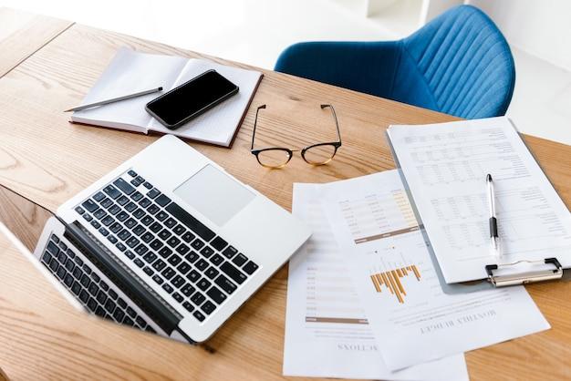Draufsicht von büromaterial, das auf holztisch liegt. laptop, zwischenablage, brille, bleistift, notizbuch. arbeitsplatz mit niemandem