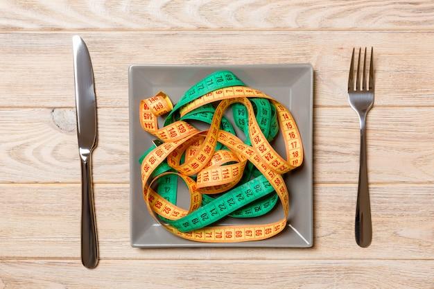 Draufsicht von bunten messenden bändern auf platte in form von spaghettis mit messer und gabel auf hölzernem. gewichtsverlust und diät