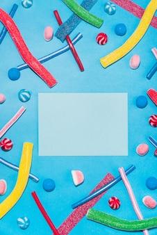 Draufsicht von bunten zuckersüßigkeiten und lollies mit umschlag in der mitte lokalisiert auf blauem hintergrund