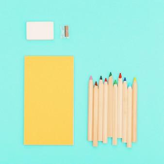 Draufsicht von buntstiften und gelbem farbskizzenblock für kreativität. satz bunte holzstifte, bleistiftspitzer, radiergummi. design hintergrund social media.