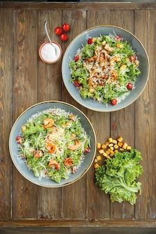 Draufsicht von caesar-salat mit garnelen- und hühnerscheiben, in der horizontalen ansicht