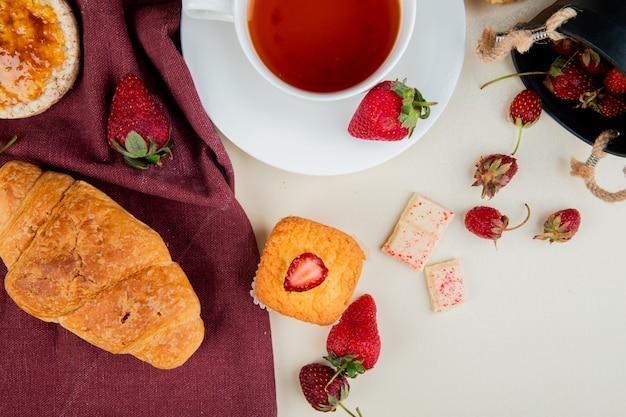 Draufsicht von crescent roll knusprigem knäckebrot auf stoff und tasse tee mit erdbeeren und cupcake mit weißer schokolade auf weißer oberfläche