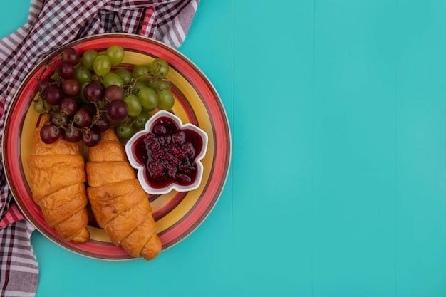 Draufsicht von croissants mit trauben und himbeermarmelade in platte auf kariertem stoff auf blauem hintergrund mit kopienraum