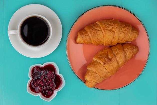 Draufsicht von croissants und himbeermarmelade mit tasse tee auf blauem hintergrund