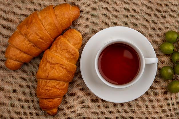 Draufsicht von croissants und tasse tee mit traube auf sackleinenhintergrund