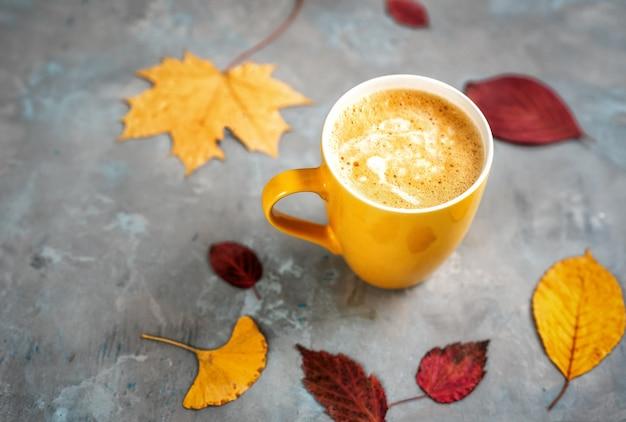 Draufsicht von cup coffe um gelbe blätter
