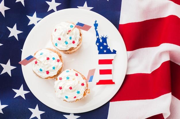 Draufsicht von cupcakes auf teller mit amerikanischen flaggen und freiheitsstatue