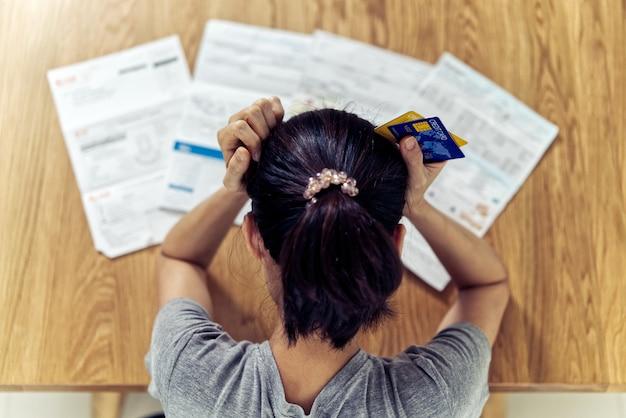 Draufsicht von den betonten jungen sitzenden asiatinhänden, die den kopf halten, sorgen sich um entdeckungsgeld, um kreditkartenschuld und alle darlehensrechnungen zu zahlen.