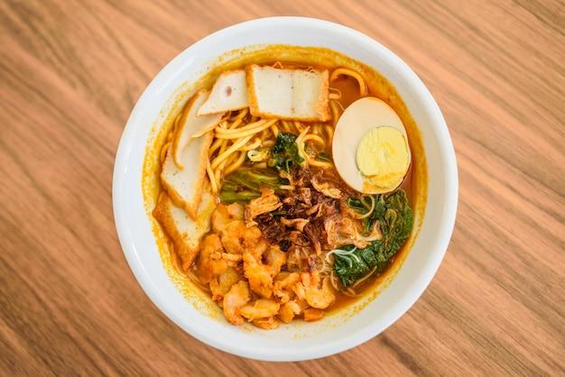 Draufsicht von den chinesischen essstäbchen nudel, eine berühmte malaysia-garnelennudel-curry-suppe essend.