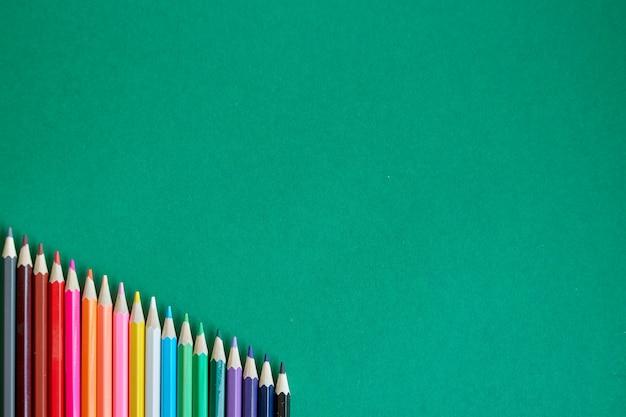Draufsicht von den farbbleistiften, die durch regenbogenfarben ausgebreitet werden, lokalisieren auf grünem hintergrund, zurück zu schule, selektiver fokus