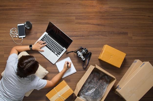 Draufsicht von den frauen, die laptop-computer vom haus auf bretterboden mit postpaket bearbeiten