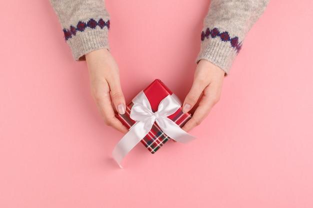 Draufsicht von den frauenhänden, die geschenkbox auf rosa halten