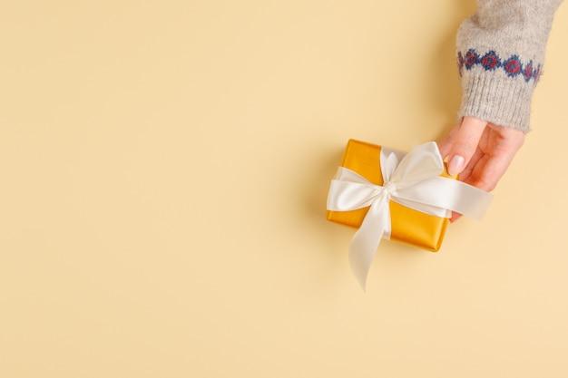 Draufsicht von den frauenhänden, die geschenkbox halten
