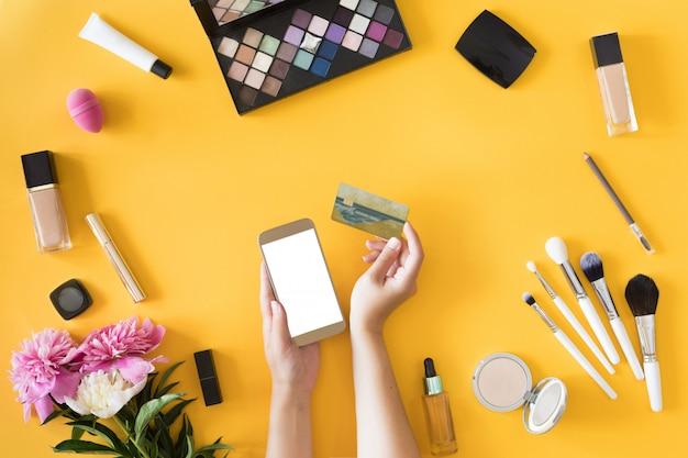 Draufsicht von den frauenhänden, die kreditkarte, on-line-einkaufskonzept, schönheitsarbeitsplatz mit laptop, handy, blumen und notizbuch, ebenenlage halten.
