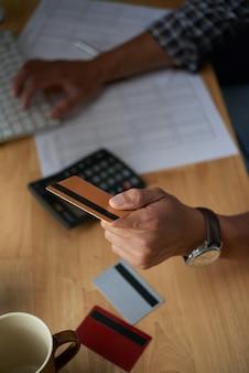 Draufsicht von den geernteten männlichen händen, die mit plastikkarte für on-line-kauf zahlen