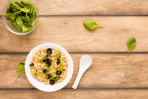 Draufsicht von den gesunden hafern geschmückt mit basilikumblatt und -olive in der schüssel auf holztisch