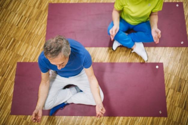 Draufsicht von den großeltern, die yoga tun