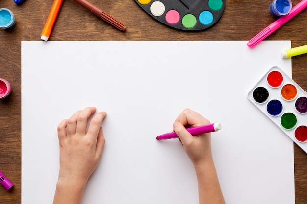 Draufsicht von den händen, die auf papier zeichnen