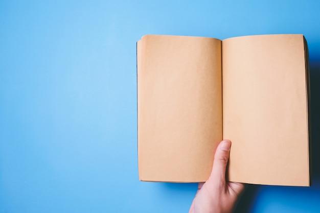 Draufsicht von den händen, die ein leeres buch bereit mit dem kopienraum bereit zum text auf blauem hintergrund halten.