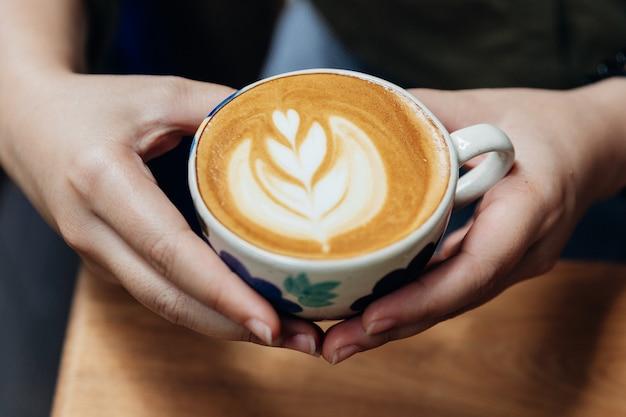 Draufsicht von den händen, die eine lattekunstherzform halten.