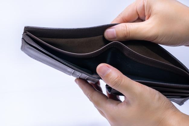 Draufsicht von den händen, die eine leere lederne geldbörse öffnen