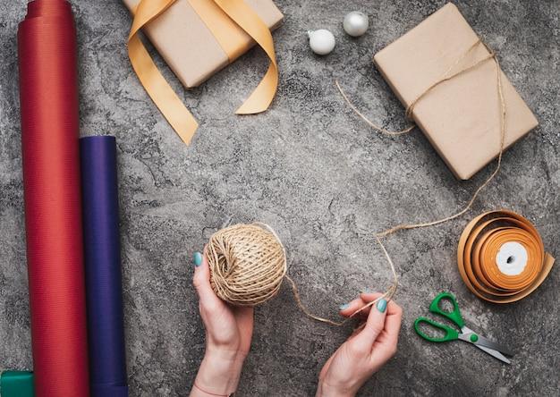 Draufsicht von den händen, die weihnachtsgeschenke verpacken