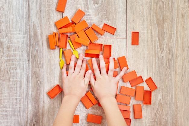 Draufsicht von den kinderhänden, die mit orange spielzeugziegelsteinen spielen. konzept der lerning kinder und der ausbildung. baby-freizeit mit sich entwickelndem spielzeug