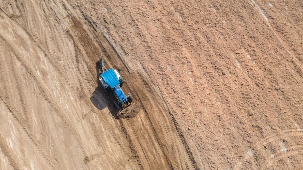 Draufsicht von den landwirtschaftlichen zugmaschinenfahrzeugen, die am feld arbeiten