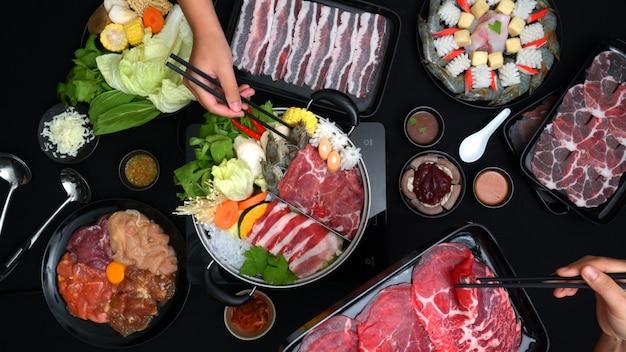Draufsicht von den leuten, die shabu-shabu im heißen topf mit frischem geschnittenem fleisch, meeresfrüchten und gemüse mit schwarzem hintergrund essen