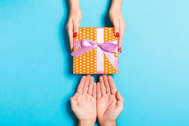 Draufsicht von den paaren, die ein geschenk auf buntem hintergrund geben und empfangen