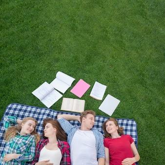 Draufsicht von den studenten, die auf picknickdecke liegen