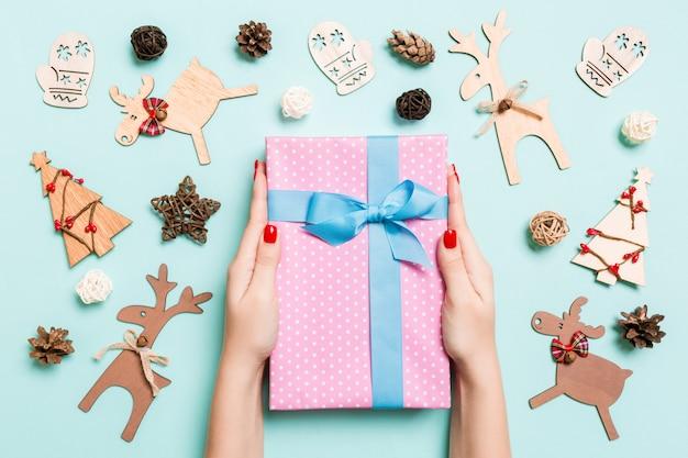 Draufsicht von den weiblichen händen, die ein weihnachtsgeschenk auf festlichem blauem hintergrund halten. weihnachtsdekoration und spielzeug. neujahrsfeiertagskonzept