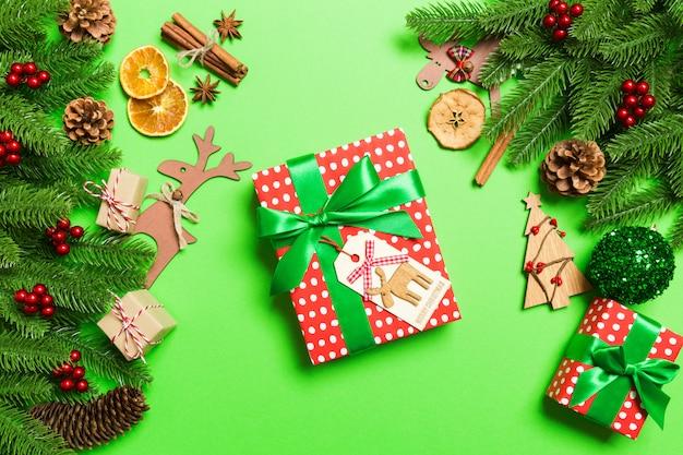 Draufsicht von den weiblichen händen, die ein weihnachtsgeschenk auf festlichem grün halten.