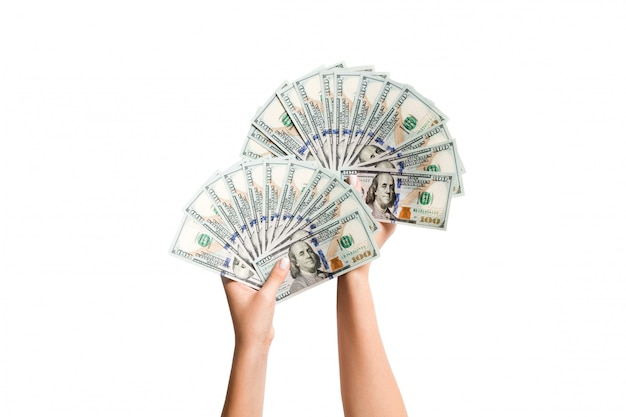 Draufsicht von den weiblichen händen, die einen fan von dollarscheinen auf lokalisiertem hintergrund geben