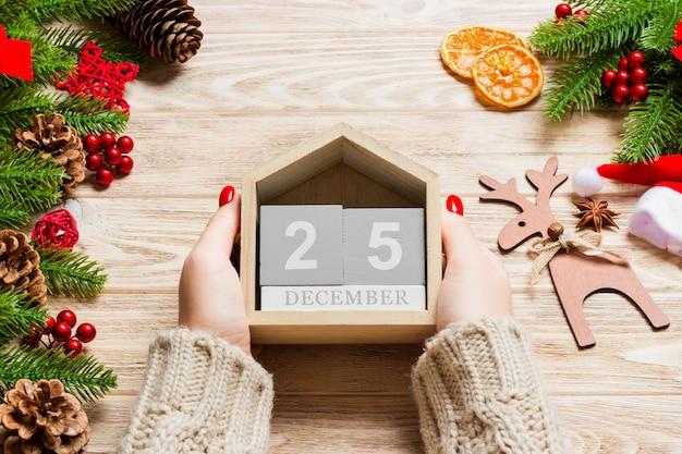 Draufsicht von den weiblichen händen, die einen kalender halten