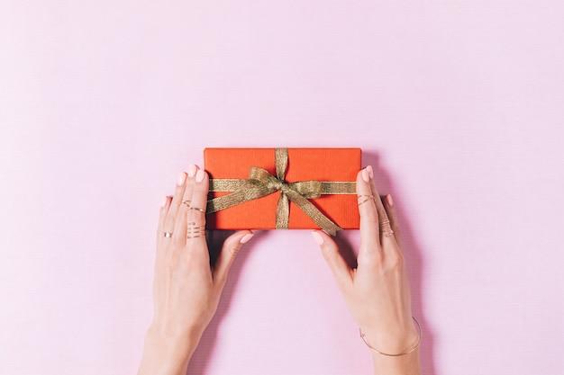Draufsicht von den weiblichen händen, die einen kasten mit geschenk halten